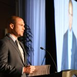 Backed by his onscreen image, Manuel Chavez III speaks at the Breakfast