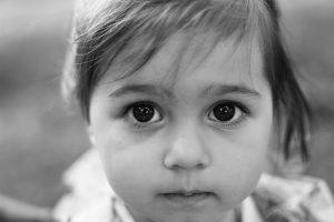 Portrait of a sad liitle girl close-up. Toned